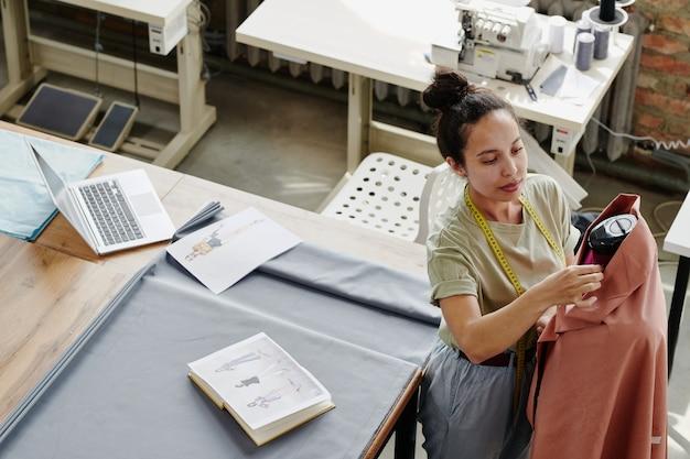 Jonge moderne werknemer van fashion design studio kledingstuk op dummy naaien tijdens het werken over nieuwe seizoenscollectie in werkplaats