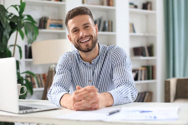 Jonge moderne zakenman die met laptop werkt terwijl hij op kantoor zit.