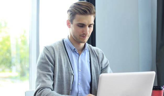 Jonge moderne zakenman die met laptop werkt terwijl hij op kantoor zit