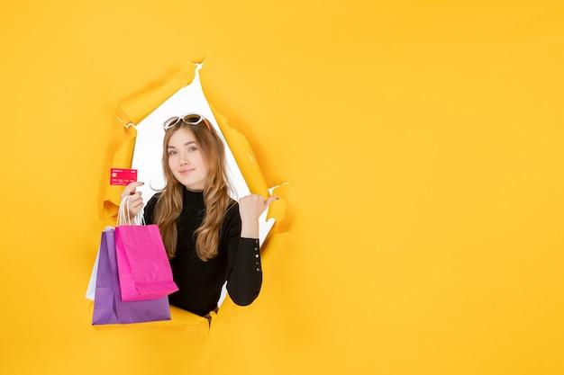 Jonge modevrouw met boodschappentassen en creditcard door een gescheurd papiergat in de muur