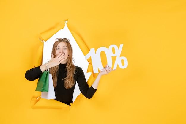 Jonge modevrouw met boodschappentassen en kortingspercentage door gescheurd papiergat in de muur