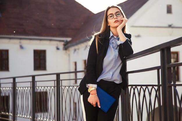 Jonge modieus geklede zakenvrouw met notebook poseren in de stad.
