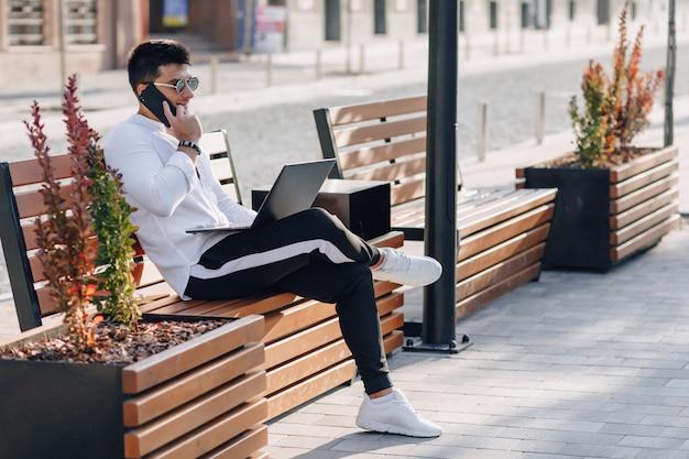 Jonge modieuze kerel in overhemd met telefoon en notitieboekje op bank op zonnige warme freelance in openlucht dag ,.
