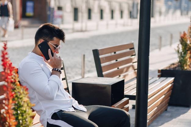 Jonge modieuze kerel in overhemd met telefoon op bank op zonnige dag in openlucht