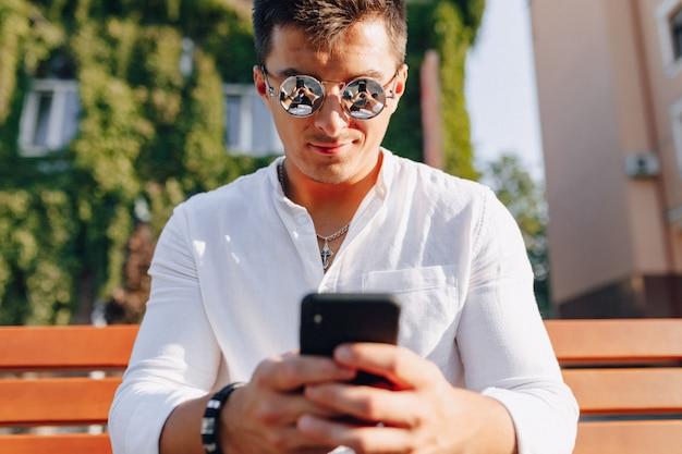 Jonge modieuze kerel in overhemd met telefoon op bank op zonnige warme dag in openlucht