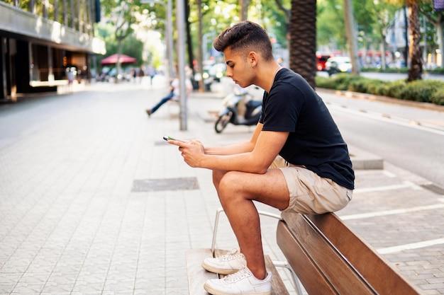 Jonge modieuze knappe man op straat van de moderne stad chatten en typen op een mobiele telefoon. communicatie en messenger concept