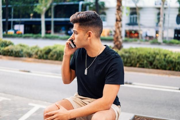 Jonge modieuze knappe man op straat van de moderne stad praten op een mobiele telefoon. communicatie concept