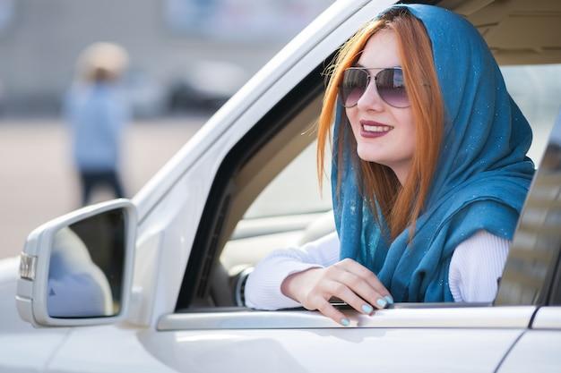 Jonge modieuze lachende vrouw bestuurder kijkt uit het raam achter het stuur van de auto.