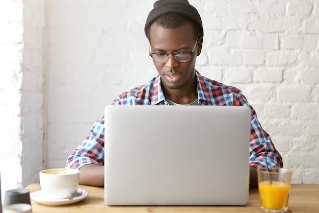 Jonge modieuze man zit in een café met laptop