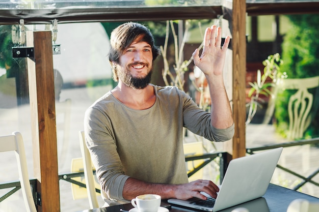 Jonge modieuze mensenzitting in koffie met laptop die zijn hand golven.