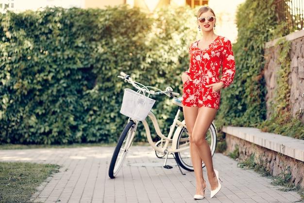 Jonge modieuze mooie sexy meisje in een rood pak in de zomer in een stad met zonnebril staat in de buurt van een fiets
