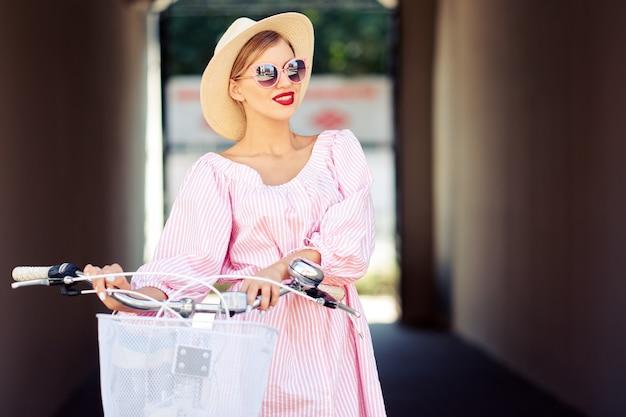 Jonge modieuze mooie sexy meisje in een roze pak en een strooien hoed rit door de stad op een fiets en lacht. het concept van een gezonde levensstijl en een stijlvolle levensstijl
