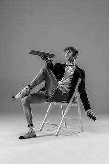 Jonge modieuze, stijlvolle man met jas en sokken die vanuit huis werken.