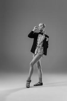 Jonge modieuze stijlvolle vrouw met jas en sokken die vanuit huis werken