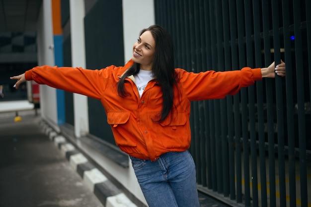 Jonge modieuze tiener meisje wandelingen door de stad in de zomer in een modieuze jas en spijkerbroek