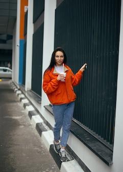 Jonge modieuze tienermeisje wandelingen door de stad en koffie drinken