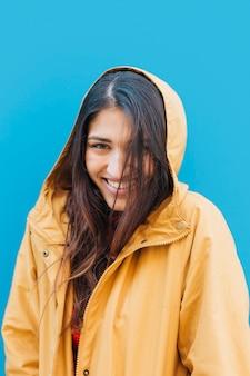 Jonge modieuze vrouw die gele hoodie voor blauwe achtergrond draagt