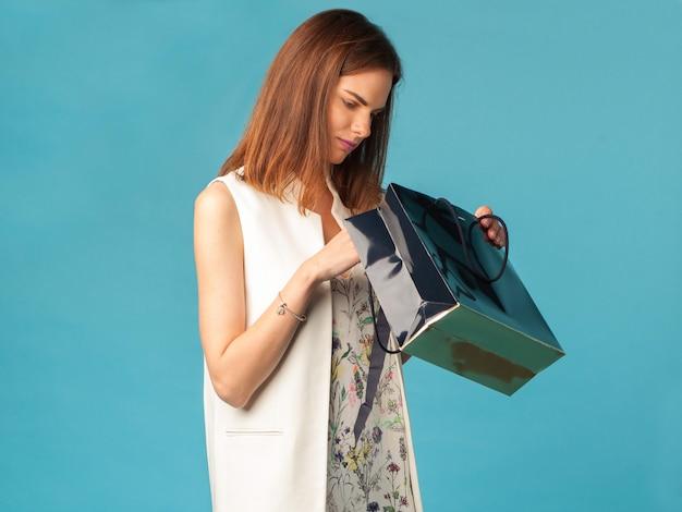 Jonge modieuze vrouw die in boodschappentas kijkt
