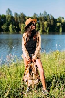 Jonge modieuze vrouw die zich dichtbij rivier met holdingsrugzak bevindt