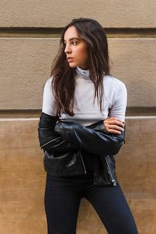 Jonge modieuze vrouw die zich tegen muur met haar gekruiste wapens bevindt