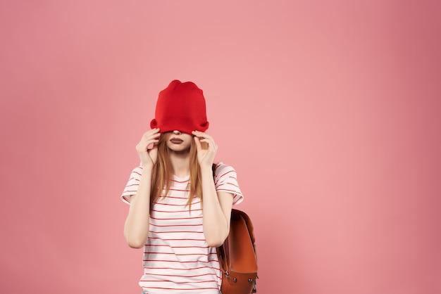 Jonge modieuze vrouw die zonnebril draagt ahah vrijetijdskleding die roze achtergrond stelt