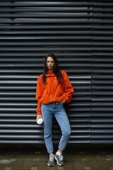Jonge modieuze vrouw hipster rusten buiten wandelen in de stad in de buurt van de muur
