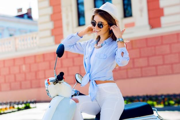 Jonge modieuze vrouw in casual outfit zittend op de scooter op straat