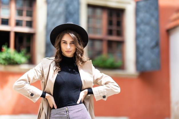 Jonge modieuze vrouw in hoed en jas poseren in straat.