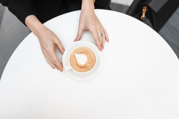 Jonge modieuze vrouw in zwarte kleding houdt een kopje met een heerlijke hete latte vast in een vintage café. koffie gourmet. goedemorgen. uitzicht van boven. detailopname.