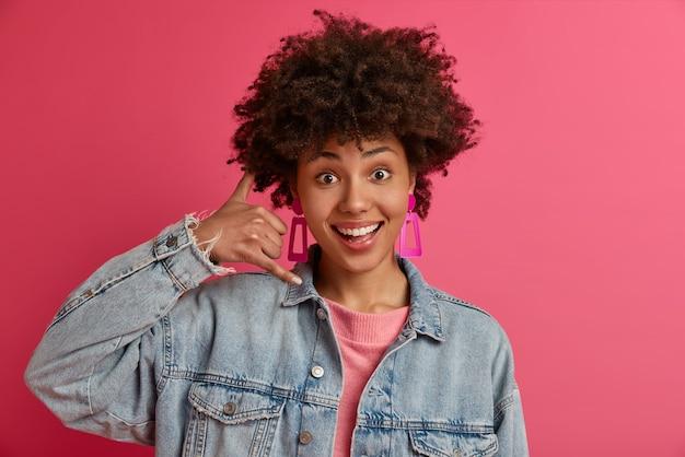 Jonge modieuze vrouw maakt telefoongebaar, vraagt om haar te bellen, drukt positieve emoties uit, draagt denim kleding, glimlacht gelukkig, geïsoleerd op roze muur. bel me terug teken. lichaamstaal