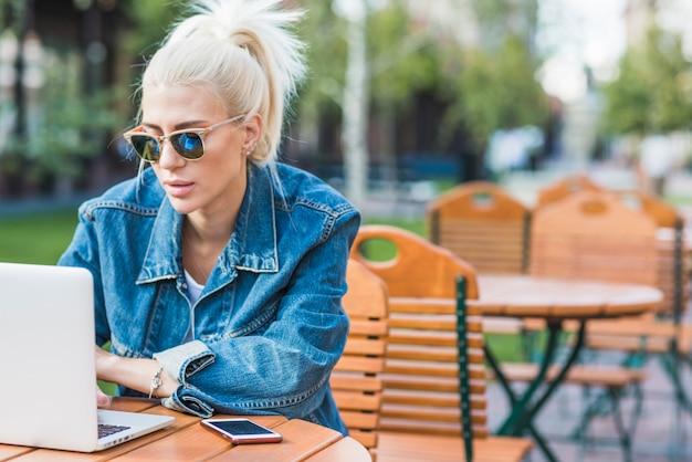 Jonge modieuze vrouw met behulp van laptop in de open lucht
