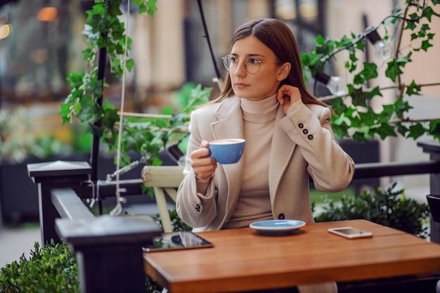 Jonge modieuze vrouwelijke influencer in café buiten zitten en koffie drinken