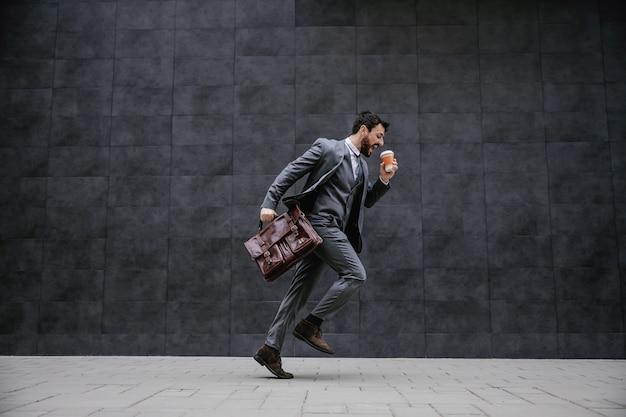 Jonge modieuze zakenman die op straat loopt. hij is te laat op zijn werk.