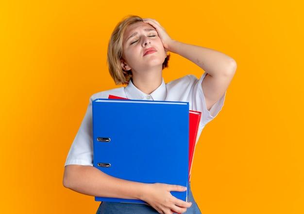 Jonge moe blonde russische meisje legt hand op het hoofd en houdt bestandsmappen geïsoleerd op een oranje achtergrond met kopie ruimte