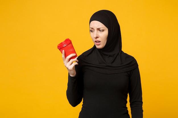 Jonge moe verdrietig boos arabische moslimvrouw in hijab zwarte kleding houdt papieren kopje koffie geïsoleerd op gele muur portret. mensen religieuze levensstijl concept.