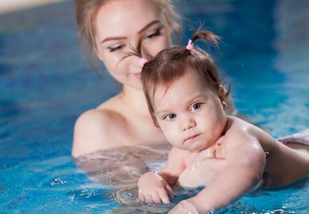 Jonge moeder baadt de baby in het zwembad.