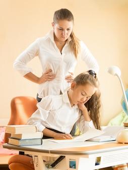 Jonge moeder boos op dochter die op bureau slaapt terwijl ze huiswerk maakt