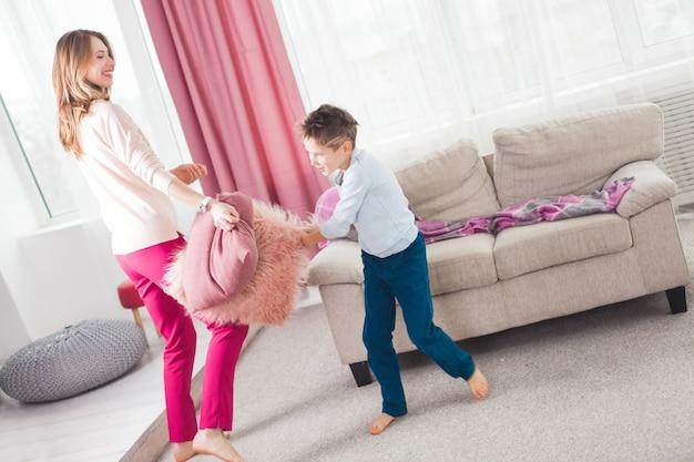 Jonge moeder die actieve spelen met haar zoon speelt. vrolijke familie binnenshuis plezier.