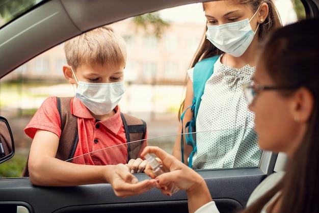 Jonge moeder die antibacteriële handdesinfecterend middel op haar kinderen toepast voordat ze naar school gaat