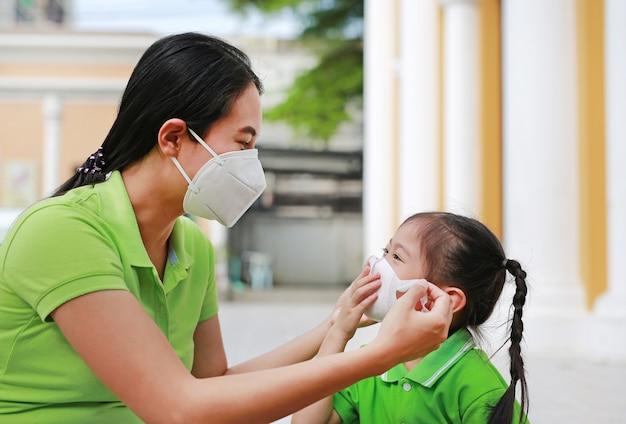 Jonge moeder die beschermend masker voor haar dochter draagt