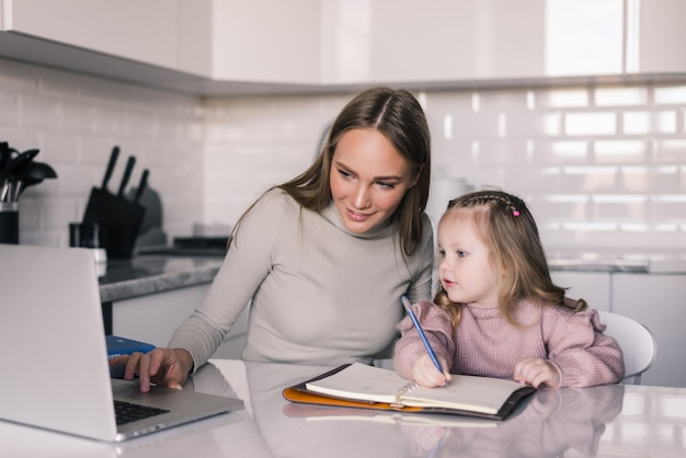 Jonge moeder die dochter met haar huiswerk helpt bij de lijst in de eetkamer