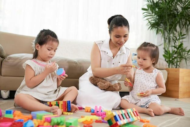 Jonge moeder die doet alsof ze haar dochtertje onzichtbaar voedsel geeft als ze met kinderen speelt...
