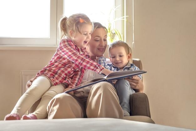 Jonge moeder die een boek leest voor haar kleine kinderen