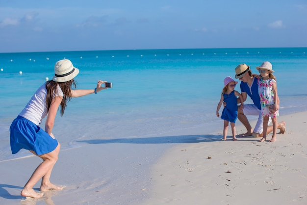 Jonge moeder die foto op telefoon van haar familie maakt bij het strand