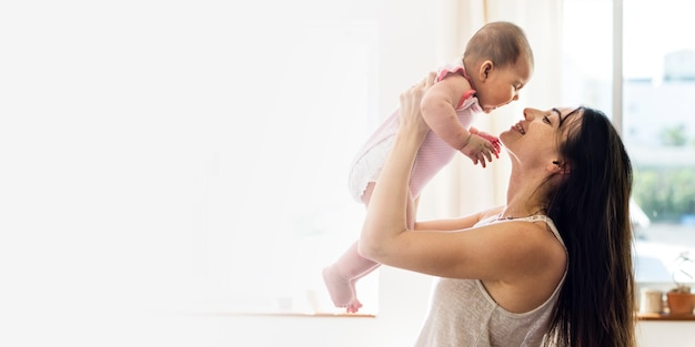 Jonge moeder die haar baby in de lucht lege ruimte houdt Gratis Foto