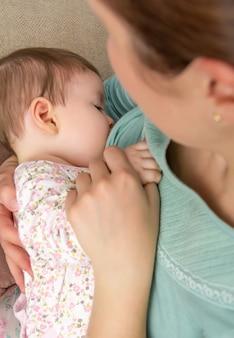 Jonge moeder die haar baby thuis borstvoeding geeft