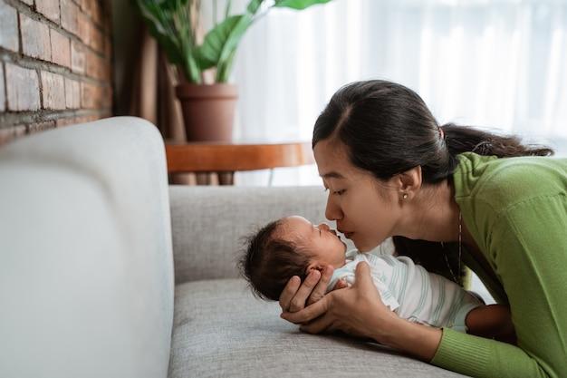 Jonge moeder die haar dochter kust