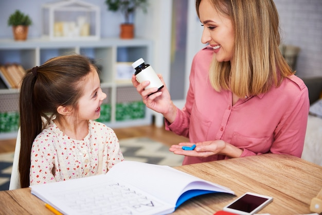 Jonge moeder die haar dochter pillen geeft terwijl ze huiswerk maakt