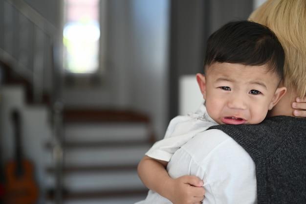 Jonge moeder die haar huilende peuterjongen vasthoudt en hem thuis probeert te kalmeren.
