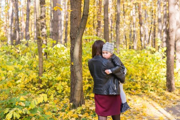 Jonge moeder die haar kind in de herfstpark vervoert